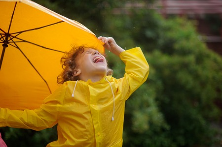 slicker: The little boy tongue catches rain drops. He has thrown back the head and has closed eyes. A hand holds an umbrella.