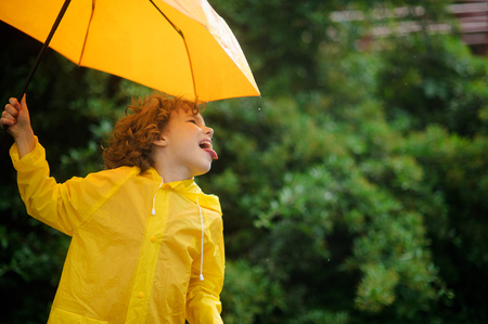 slicker: Cheerful boy with a bright yellow umbrella in raincoat. Laddie protrude tongue and catches rain drops. He is amused by such game.