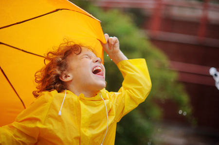 slicker: The little boy stand in the rain and tongue catches rain drops. He has thrown back the head and has closed eyes. A hand holds an umbrella. Stock Photo