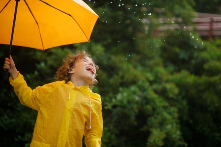 Boy with a yellow umbrella catches tongue rain drops. He likes such game. The boy has a good mood.