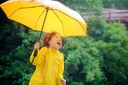 slicker: Laddie with a yellow umbrella catches tongue rain drops. He likes such game. The boy has a good mood. Behind the back there is a magnificent green bush Stock Photo