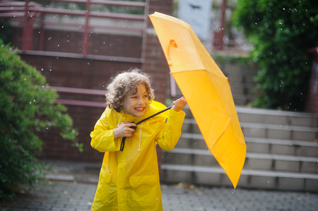 tries: The amusing little boy in a yellow raincoat and with a yellow umbrella stand in the rain. Large drops of a rain fall to it on the head, and he tries to open an umbrella.