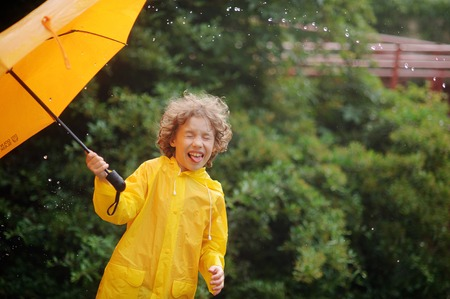 slicker: Boy of 8-9 years with an umbrella in a hand to stand in the rain. Large drops of a rain fall to it on the head. Little fellow closed eyes from delight.Behind the back there is a magnificent green bush