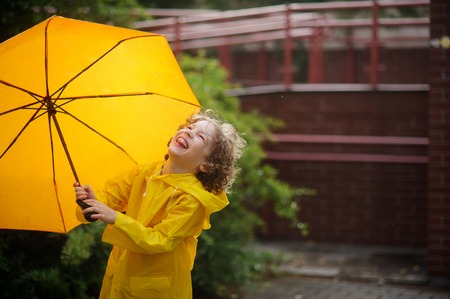 jaunty: The boy with a yellow umbrella rejoices to a rain. The child is dressed in a bright yellow raincoat. He is in the yard and laughing looks up. The boy has blonde curly hair and a nice face. Stock Photo