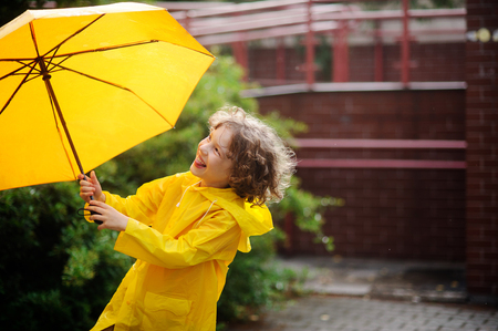 Laddie 8-9 year with a curly fair hair admires the yellow umbrella. On a face of the boy a pleased smile.