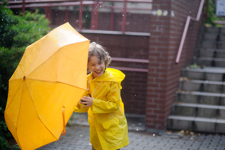 jaunty: Boy 8-9 years walk with a yellow umbrella in the yard during rain. He very much likes such weather. The child has closed eyes and laughs from pleasure. Stock Photo