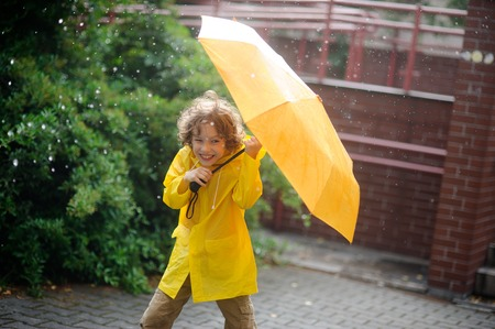 Boy of 8-9 years in the rain. It holds a yellow umbrella. The child with a smile looks in the camera having squinted. It has wild curly hair and a nice face. The boy is dressed in yellow raincoat.