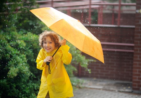 slicker: The boy in a bright yellow raincoat to stand under a pouring rain. In hands it squeezes a yellow umbrella. The boy laughs looking in the camera. It likes to walk in the rain. Stock Photo