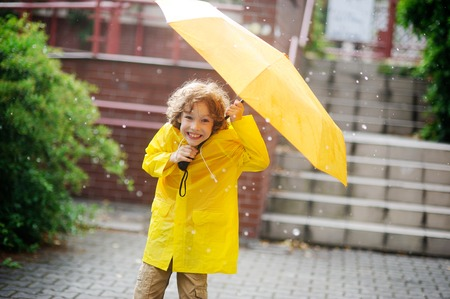 jaunty: The little fellow in a bright yellow raincoat is in the yard under a pouring rain. Two hands he holds an open yellow umbrella. Large drops of a rain. To the boy it is very cheerful. He with a smile looks in the camera.