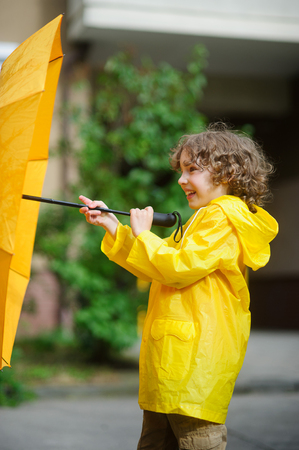 Boy in a yellow raincoat with an umbrella in hands. The child is in the yard of the house. The boy with a cheerful smile opens a yellow umbrella.