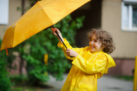 constrain: The boy 8-9 years in a bright yellow raincoat tries to hold an umbrella from wind flaws. He holds an umbrella with two hands. Child is in the yard of the house. He has a good mood