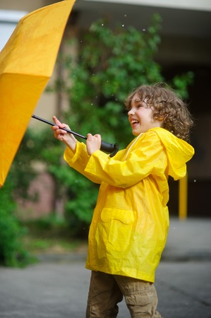 Laddie 8-9 years in a bright yellow raincoat tries to hold an umbrella from windflaws. The boy holds an umbrella with two hands. To him it is cheerful.