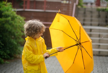 The boy in a bright yellow raincoat opens an umbrella during a rain. The child is in the yard of the house. Drops of a rain fall to it on the head. The boy with a cheerful smile opens a yellow umbrella.