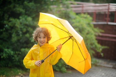 The cheerful boy with a yellow umbrella is in the yard under a rain. He holds an open yellow umbrella. Large drops of a rain. To the boy it is very cheerful. He with a smile looks in the camera. Stock Photo