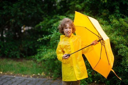 The boy in a raincoat with an umbrella in hands. The cute little fellow dressed in a yellow raincoat holds a yellow umbrella. He looks in the camera. Behind his back magnificent green vegetation. Stock Photo