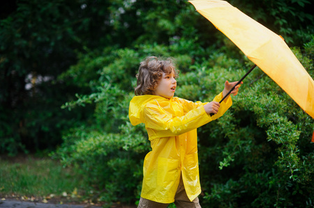 Curly boy in a bright yellow raincoat with an umbrella against a magnificent green bush.