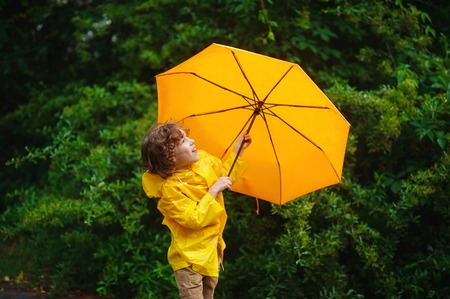 Boy of 8-9 years with a yellow umbrella. Cute chappie dressed in a yellow raincoat. The rain has ended and the boy with a cheerful smile looks in the sky. Behind his back a beautiful green bush