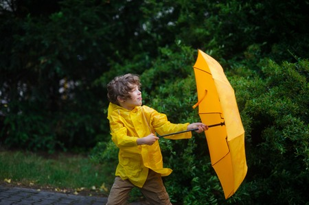 Rushes of heavy wind pull out an umbrella from the boys hands. Little fellow dressed in a bright yellow raincoat strong holds an umbrella with hands. Wind frays the boys hair.