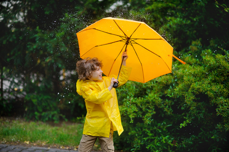 Little fellow walks in park with an umbrella under a pouring rain. Large drops fall on a yellow umbrella. The boy likes such weather and he smiles. Stock Photo