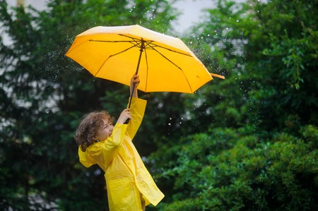 slicker: Laddie with a bright yellow umbrella in the rain. He loves a rain and rejoices. Behind the back of the boy a beautiful wet bush.