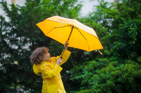 Laddie with a bright yellow umbrella in the warm summer rain. He loves a rain and rejoices. Behind the back of the boy a beautiful greens of park.