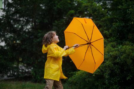 Fair-haired fellow of 8-9 years walks under a warm summer rain with a yellow umbrella. The boy is dressed in a bright yellow raincoat. He plays with a rain and rejoices.