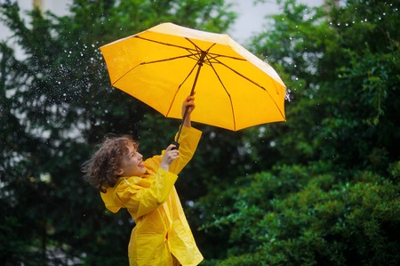 perky: Chappie with a bright yellow umbrella in the warm summer rain. He loves a rain and rejoices. Large rain drops fall on an umbrella dome. Behind the back of the boy a beautiful greens of park.