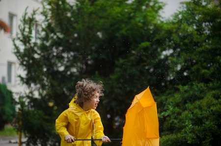 Laddie in a bright yellow raincoat and with an umbrella resists to rushes of strong wind. He hardly holds an umbrella. A fair hair of the boy was disheveled by wind.