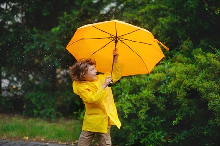 Boy of 8-9 years stand in the rain with a big yellow umbrella. He likes such weather. He cheerfully laughs. Behind the back of the child a magnificent green bush.