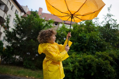 Onset of wind has wrest an umbrella in boys hands. But it is pleasant to the child. He to stand under warm rain and laughs. Stock Photo