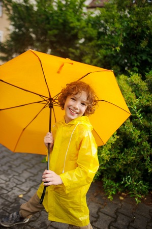 The cute boy of 8-9 years under a yellow umbrella. The boy in a bright yellow raincoat holds a big umbrella in hand. The child looks in the camera with a smile. Behind magnificent wet bush.
