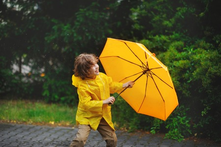 8-9 years boy walking in the rain. The little fellow in a yellow raincoat with a yellow umbrella walks in park under a small summer rain. On his face a smile. Walk it gives pleasure.
