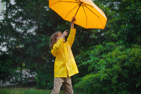 Chappie with a bright yellow umbrella and in a raincoat under warm summer rain. He loves a rain and rejoices. He cheerfully plays with rain drops. Behind the back of the boy a beautiful greens of park