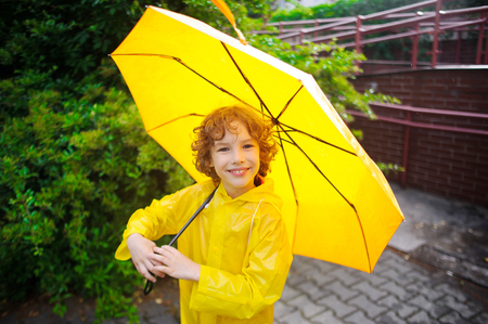 The nice fellow of 8-9 years under a yellow umbrella. The boy in a bright yellow raincoat holds a big umbrella in hand. The child looks in the camera with a smile. It likes to walk under a drizzle on the wet sidewalk.