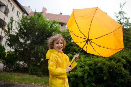 slicker: The strong flaw has turned out an umbrella dome in the boys hands. The little boy with pleasure walks in the yard in the rain. Large rain drops fall on his head.