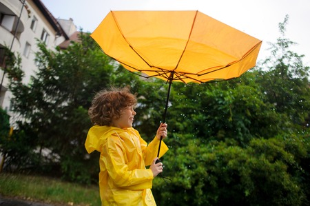 slicker: Strong wind has wrest an umbrella in boys hands. Strong wind has wrest an umbrella in boys hands. But it is pleasant to the child. He to stand under warm rain and laughs.