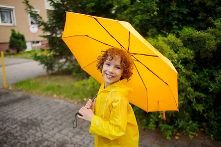 Cheerful boy of 8-9 years under a yellow umbrella. The child with a smile looks in the camera. It has humid curly hair and a nice face. The boy is dressed in a bright yellow raincoat. Stock Photo