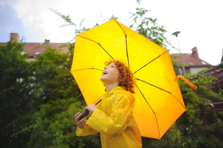 slicker: The nice fellow of 8-9 years holds a big yellow umbrella. The boy in a bright yellow raincoat. The child looks in the sky with a smile. It likes to walk under a drizzle.