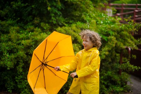 The boy holds an umbrella in hand, but doesnt hide under him from a rain. He likes to be under a warm summer rain. Child joyfully smiles. Behind him magnificent wet bush.