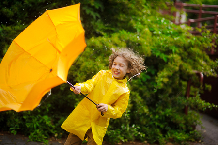 The boy in a bright yellow raincoat with effort holds an umbrella from wind. Strong wind pulls out a yellow umbrella from his hands. Wind has disheveled hair, drops of a rain drip to him on the head.