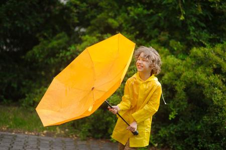 De jongen van 8-9 jaar houdt een paraplu vast met de uitgedraaide koepel tegen sterke wind. Voor het kind is het heel opgewekt. Hij heeft de ogen gesloten van plezier. Op een achtergrond prachtige natte struik