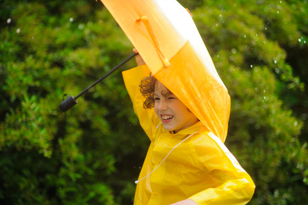 Boy of 8-9 years in a yellow raincoat and with an umbrella stand in the rain. The child likes such weather and he smiling. On a background magnificent wet bush