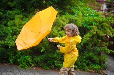 The fellow is dressed in a bright yellow raincoat. He likes to walk in the rain and the boy cheerfully laughs. Stock Photo