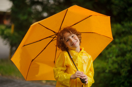 nice face: The boy with a yellow umbrella. He is dressed in a bright yellow raincoat. The boy has a nice face and curly hair.