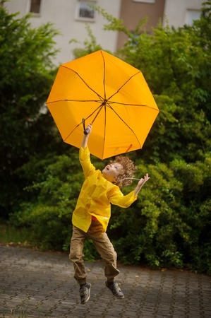 The little fellow flies over the yard with a yellow umbrella in a hand. As if picked up by strong wind. On face of the boy expression of delight. On a background magnificent green bush and house. Stock Photo