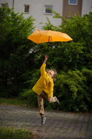 The boy in a bright yellow raincoat flies over the earth with an umbrella in a hand. As though the flaw has picked up an easy body. From delight the boy has thrown back the head. Stock Photo
