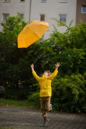 The boy of 8-9 years in a bright yellow raincoat tries to catch the departing yellow umbrella. Strong wind has pulled out an umbrella from the boys hands.