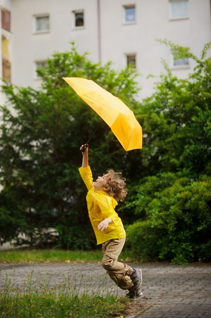 Cheerful little boy runs on the yard of the house with an umbrella in a hand. The boy tries to hold an umbrella from wind. Fair hair was disheveled, on a face a happy smile.