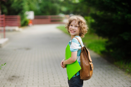 scholastic: Schoolboy of 8-9 years stand in a half-turn to the camera and joyfully smiles. The boy has a nice face, a fair hair, an open look. It has behind shoulders a satchel. Green folder in hands .