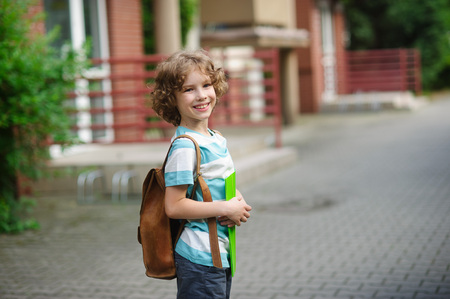 schoolyard: The pupil of elementary school stand on a schoolyard and smiles. It has a nice face and blue eyes. Behind shoulders at the boy a school backpack. Stock Photo